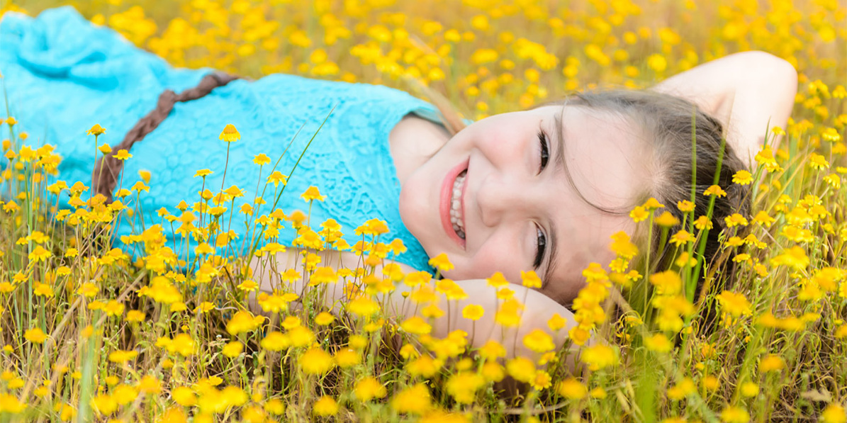 image of little girl lying in yellow flowers