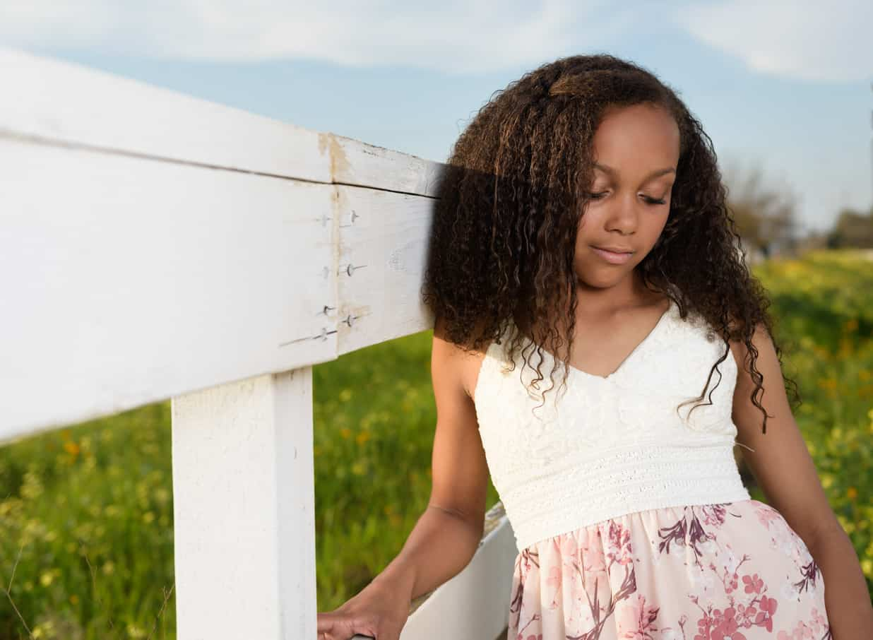 image of teen leaning up on white fence