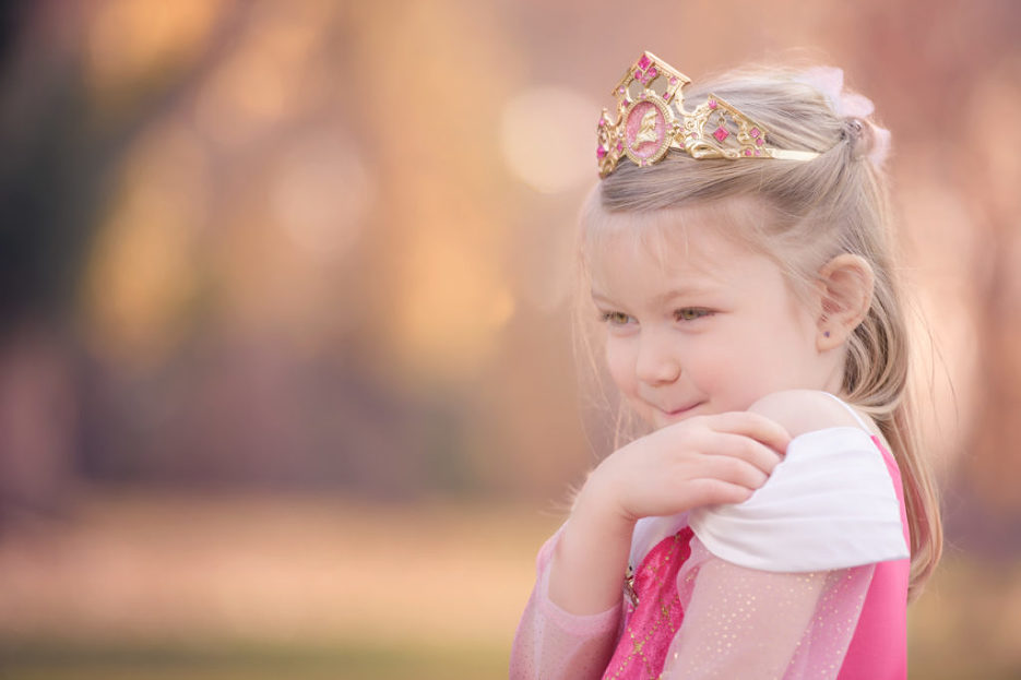 little girl laughing into her hand wearing princess aurora dress
